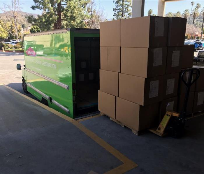 Brown boxes loaded into green truck